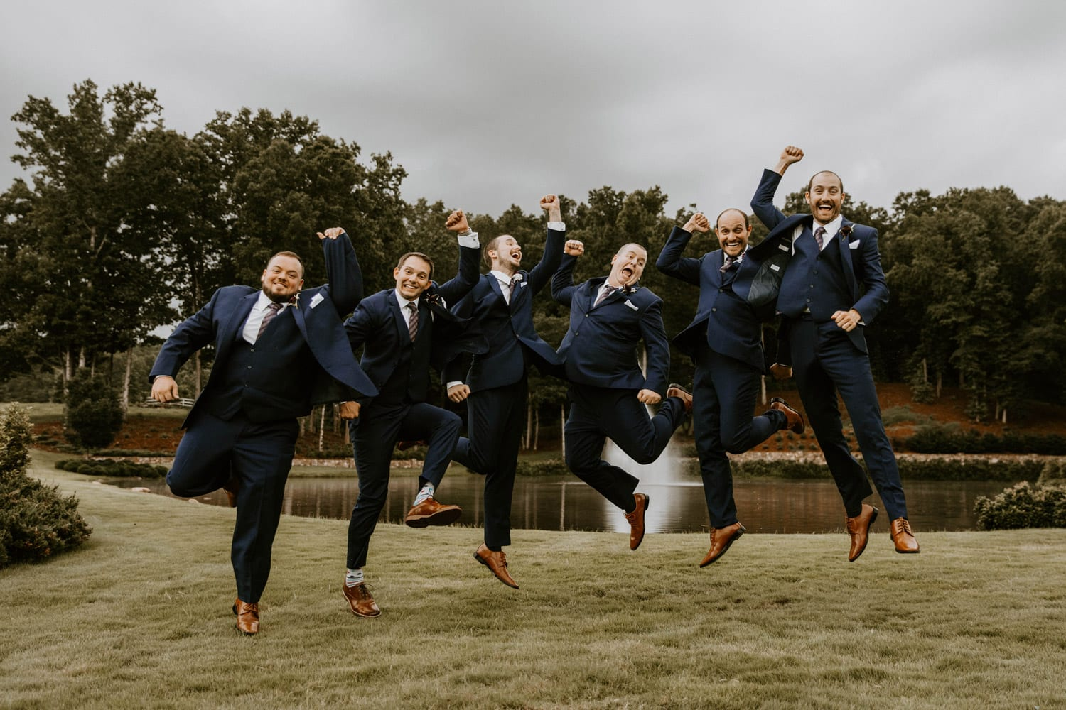 Groom and groomsmen jumping in the air
