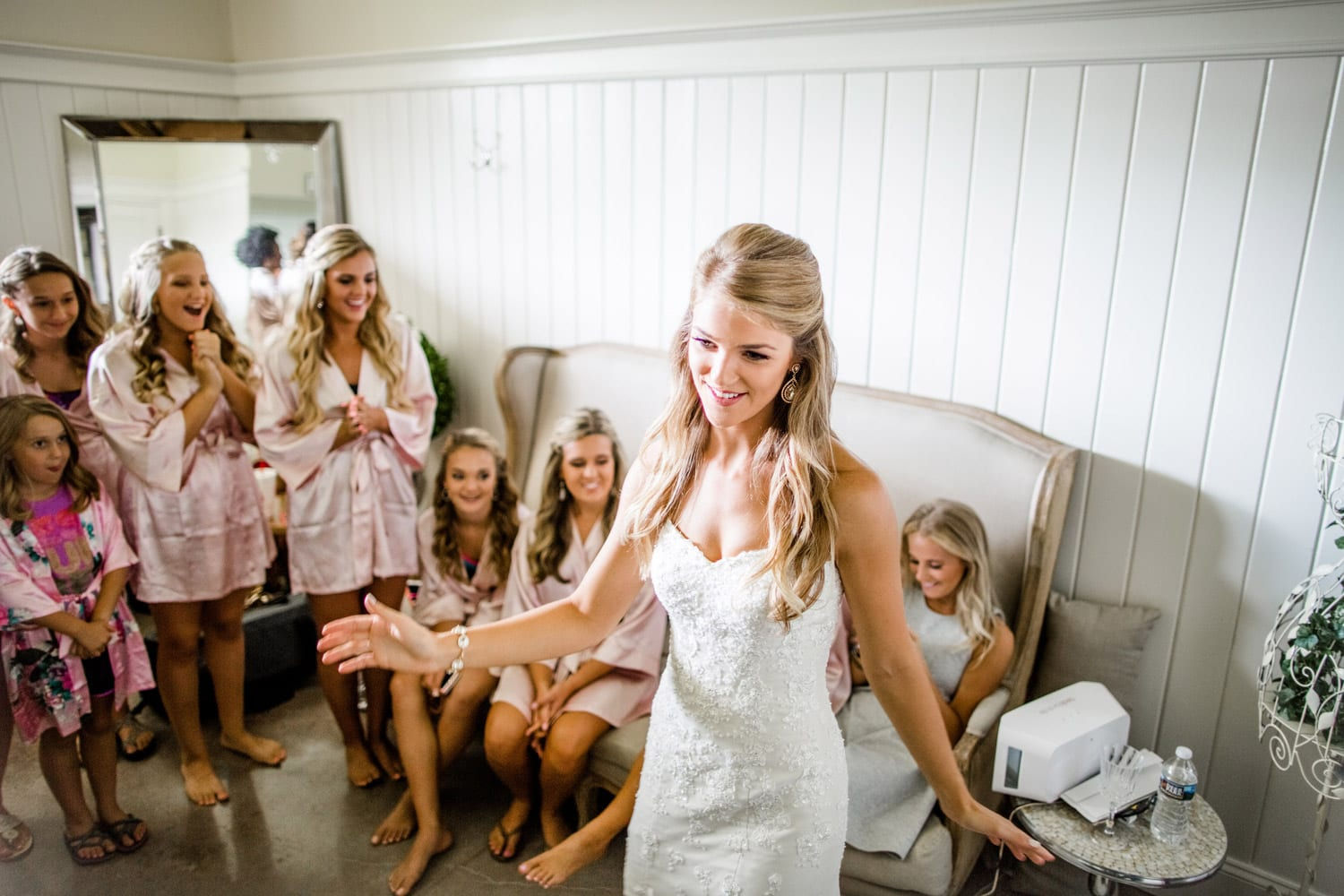 Bride showing off dress in bridal room with bridesmaids