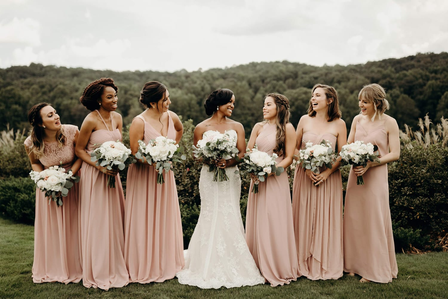 Bride and bridesmaids outside holding flowers