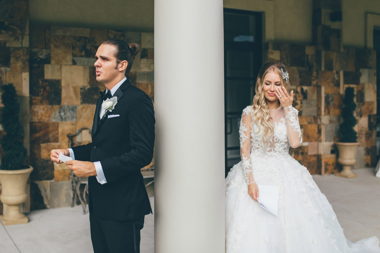 Groom and bride read letters next to column