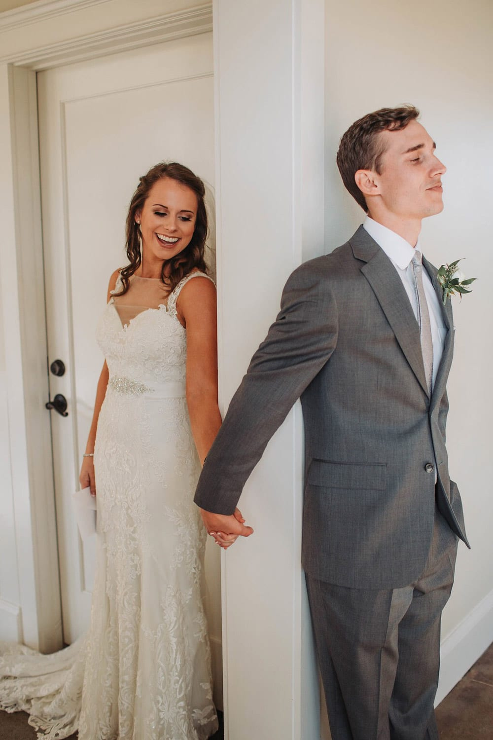 Bride and groom hold hands around corner