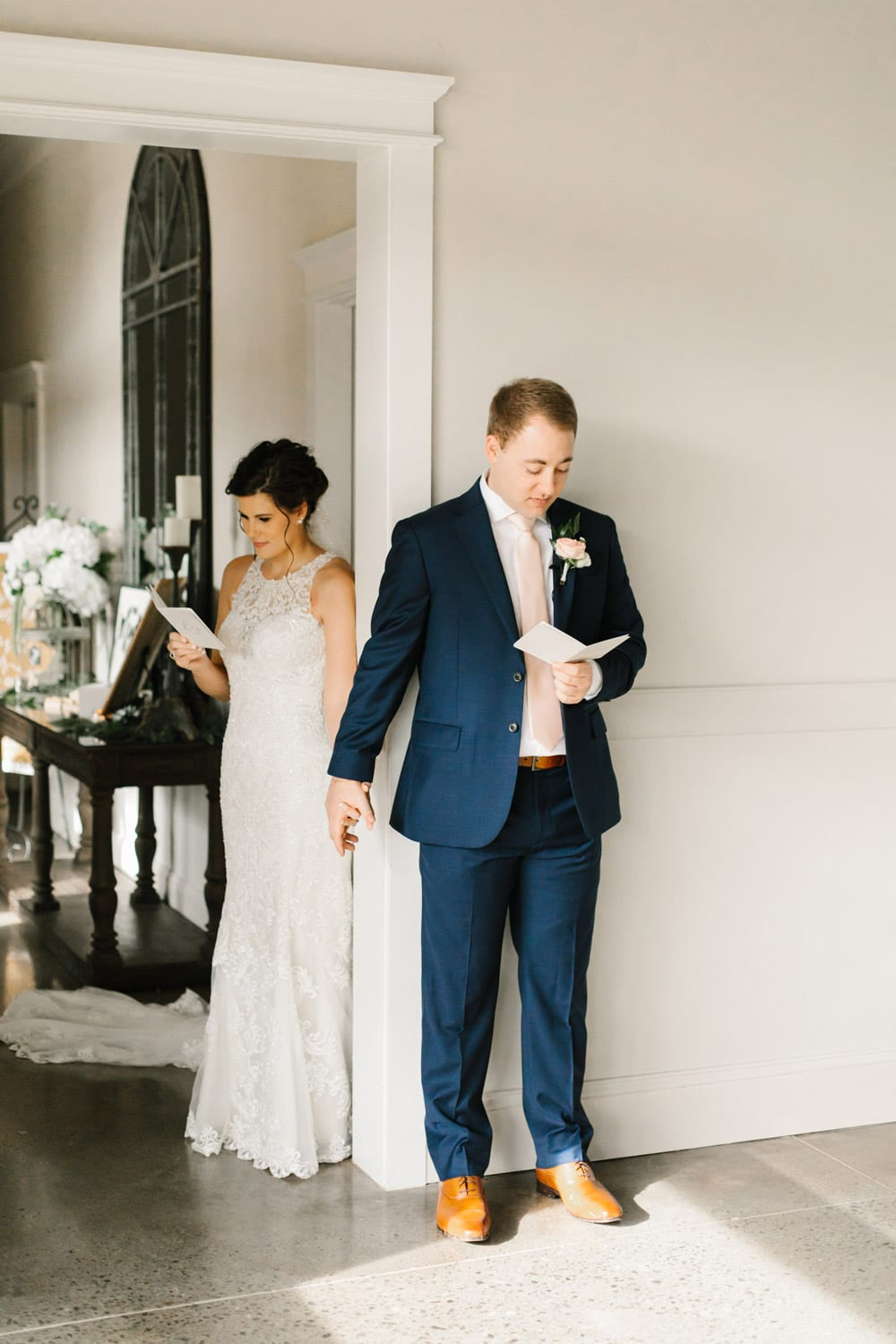 Bride and groom hold hands around corner and read letters