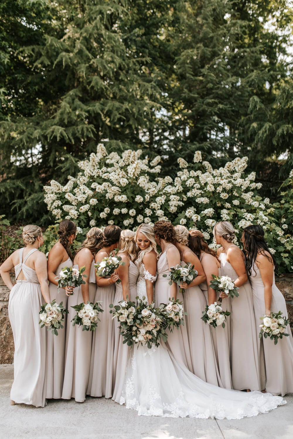 Bride and bridesmaids pose with flowers outside