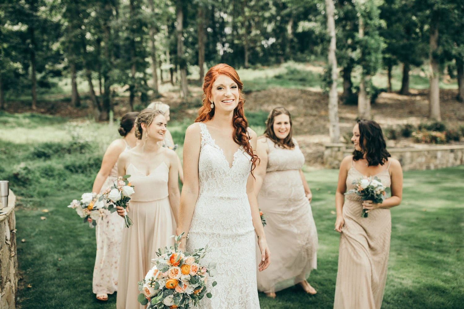 Bride and bridesmaids walking outside with flowers
