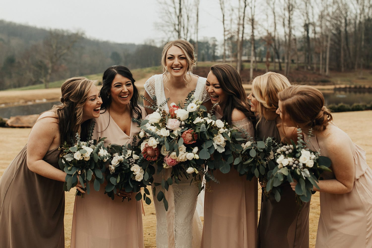 Bride and bridesmaids pose with flowers in front of water