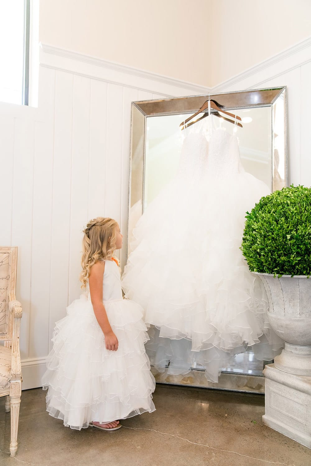 Flower girl looks at dress hanging on mirror