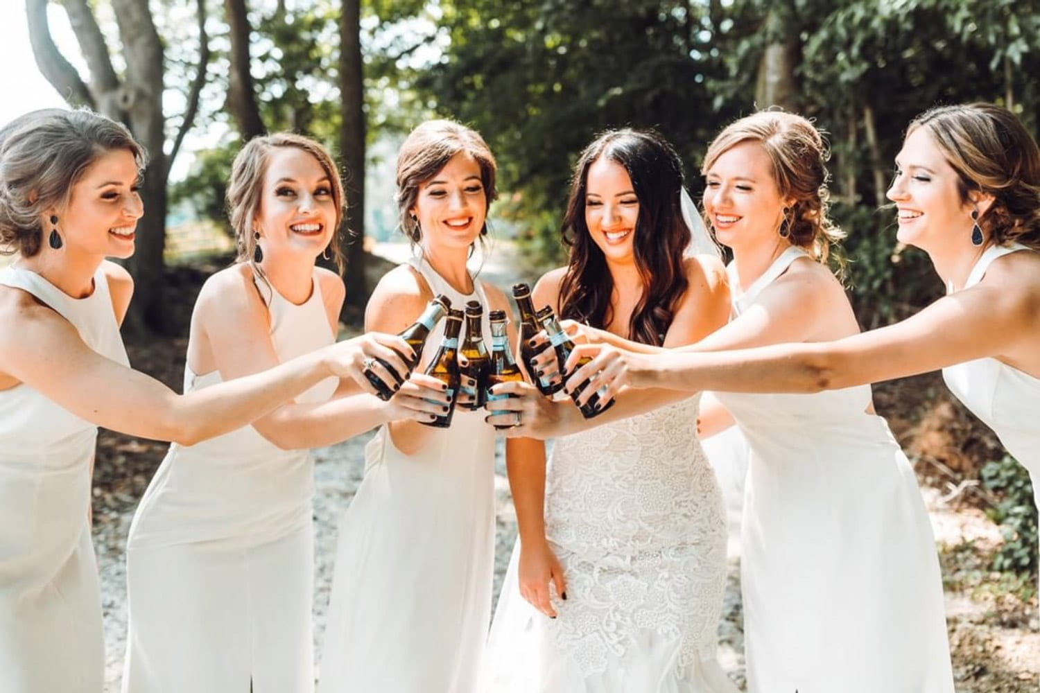 Bride and bridesmaids toast outside