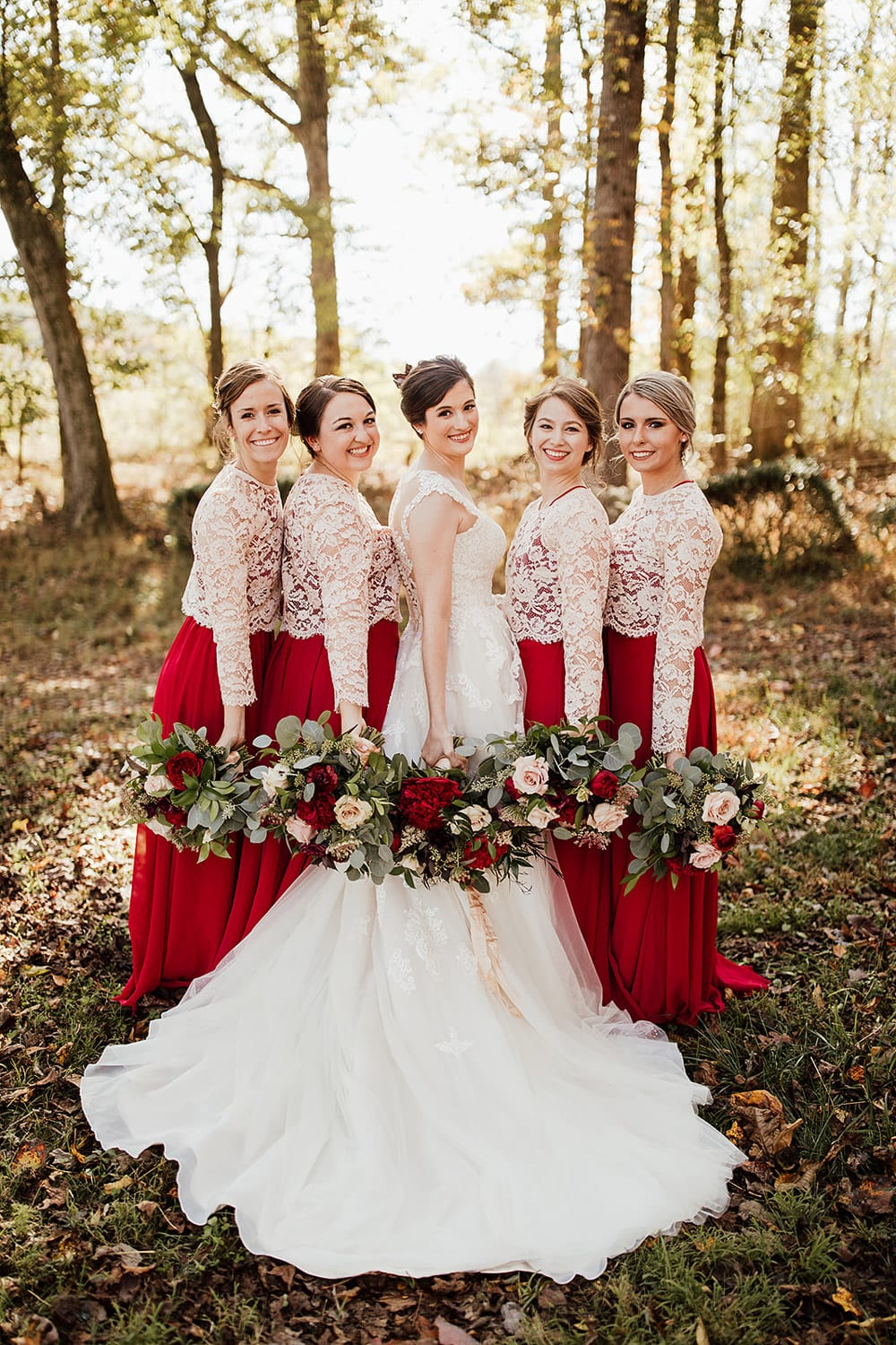 Bride and bridesmaids pose with flowers in forest
