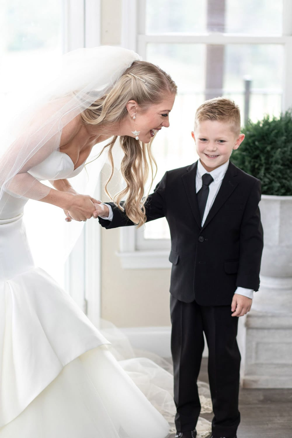 Bride holds ring boy's hand