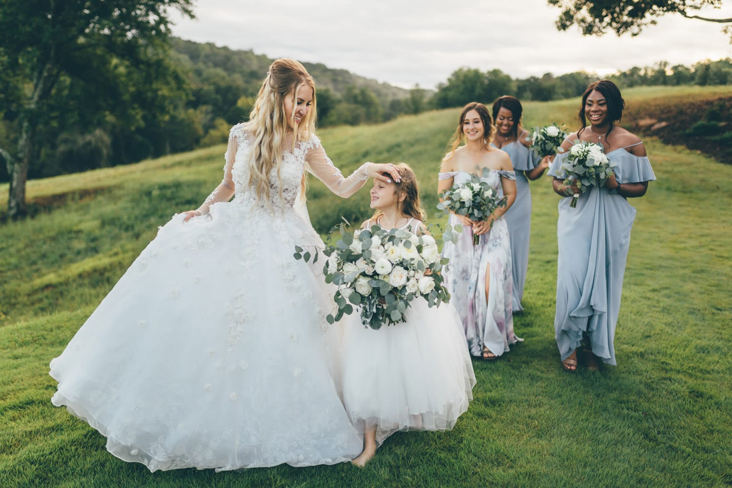 Bride walks outside with bridesmaids and flower girl