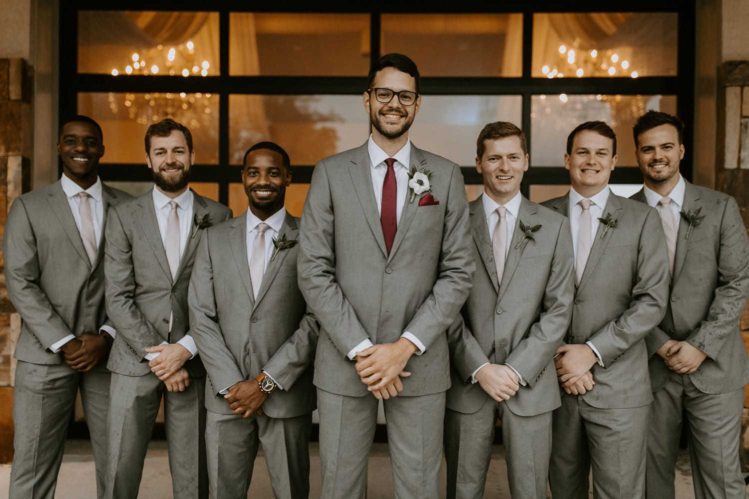Groom and groomsmen in front of venue window