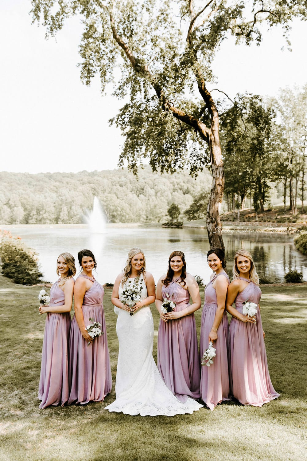 Bride and bridesmaids standing in front of fountain