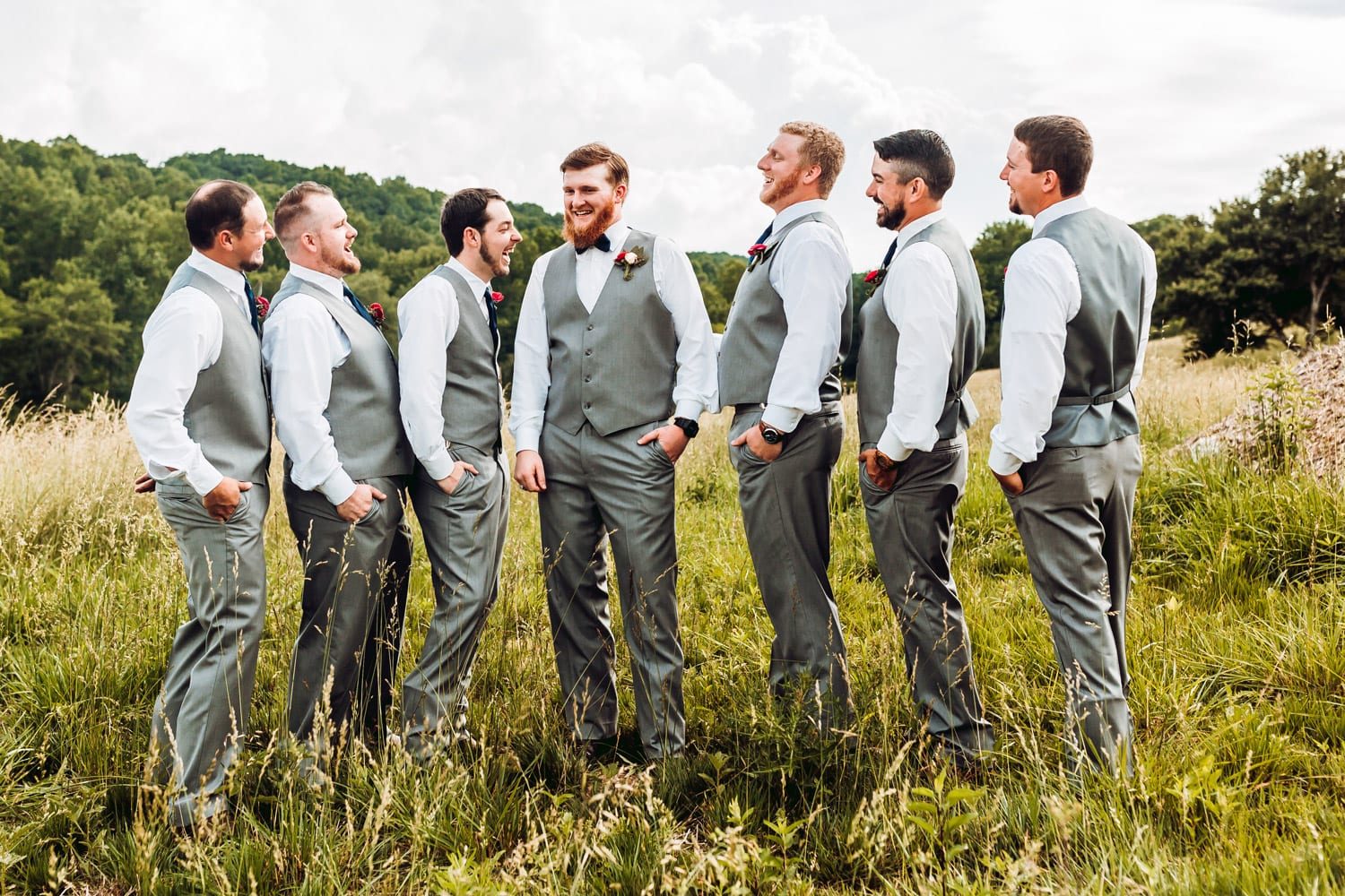 Groom and groomsman standing in pasture