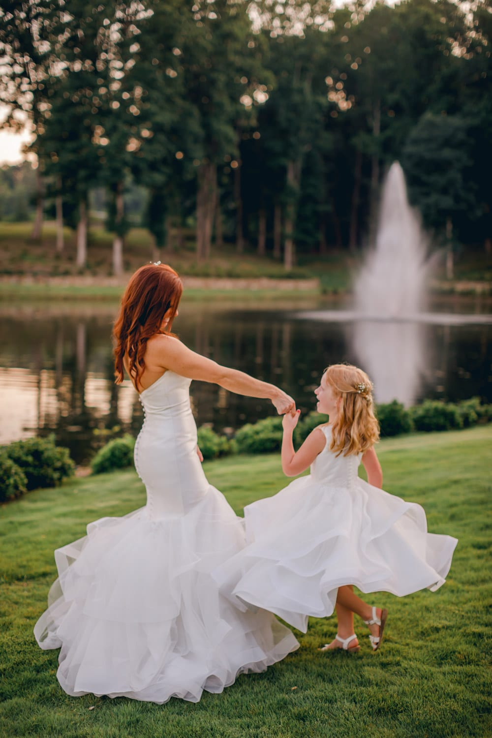 Bride and flower girl dancing in front of fountain