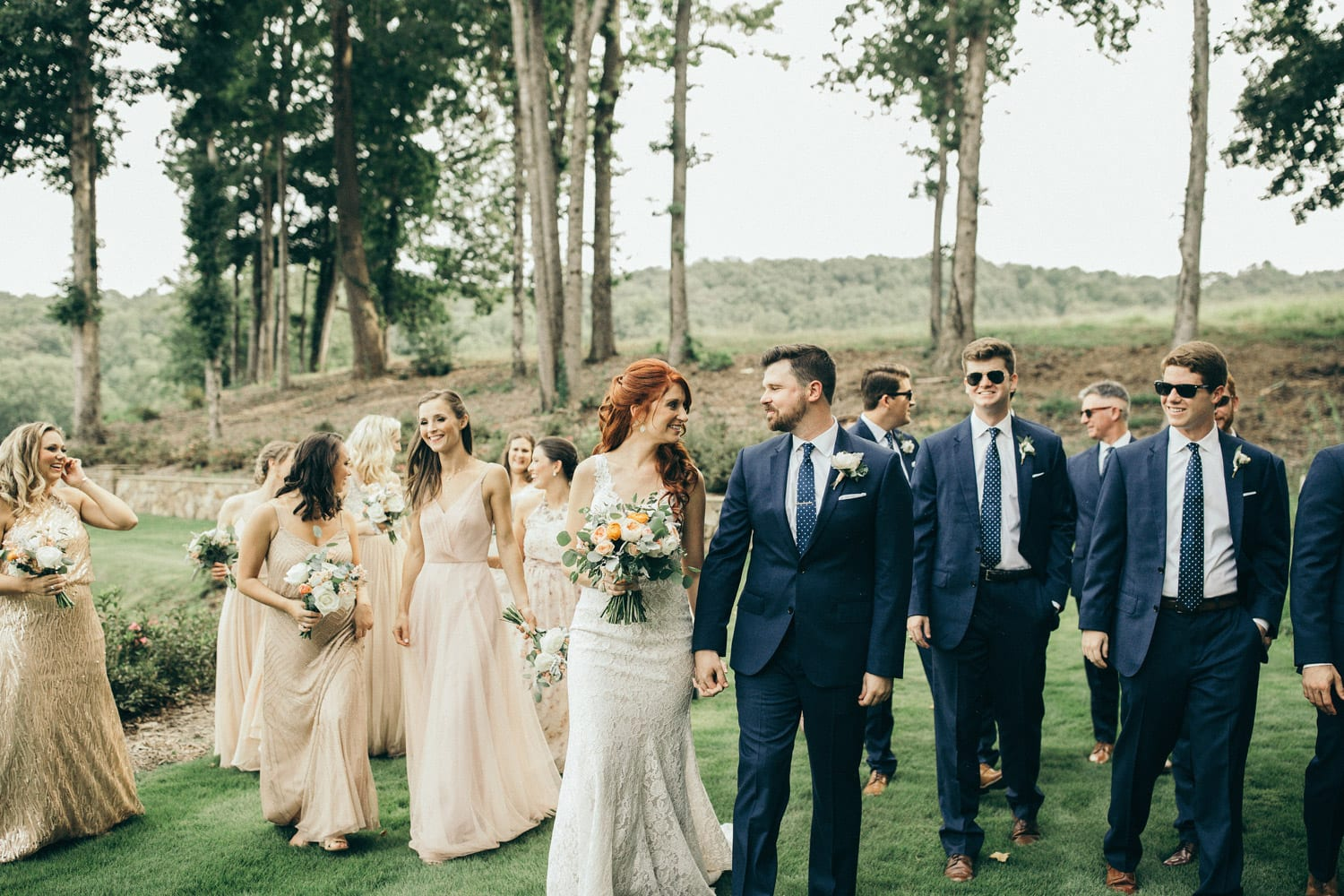 Bridal party walks outside in the grass