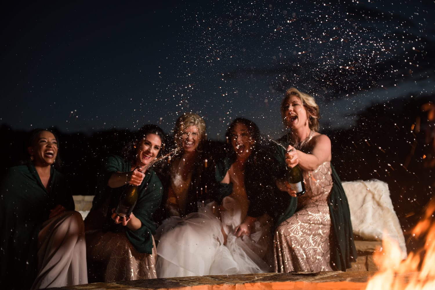 Bride and bridesmaids open champagne by the fire pit