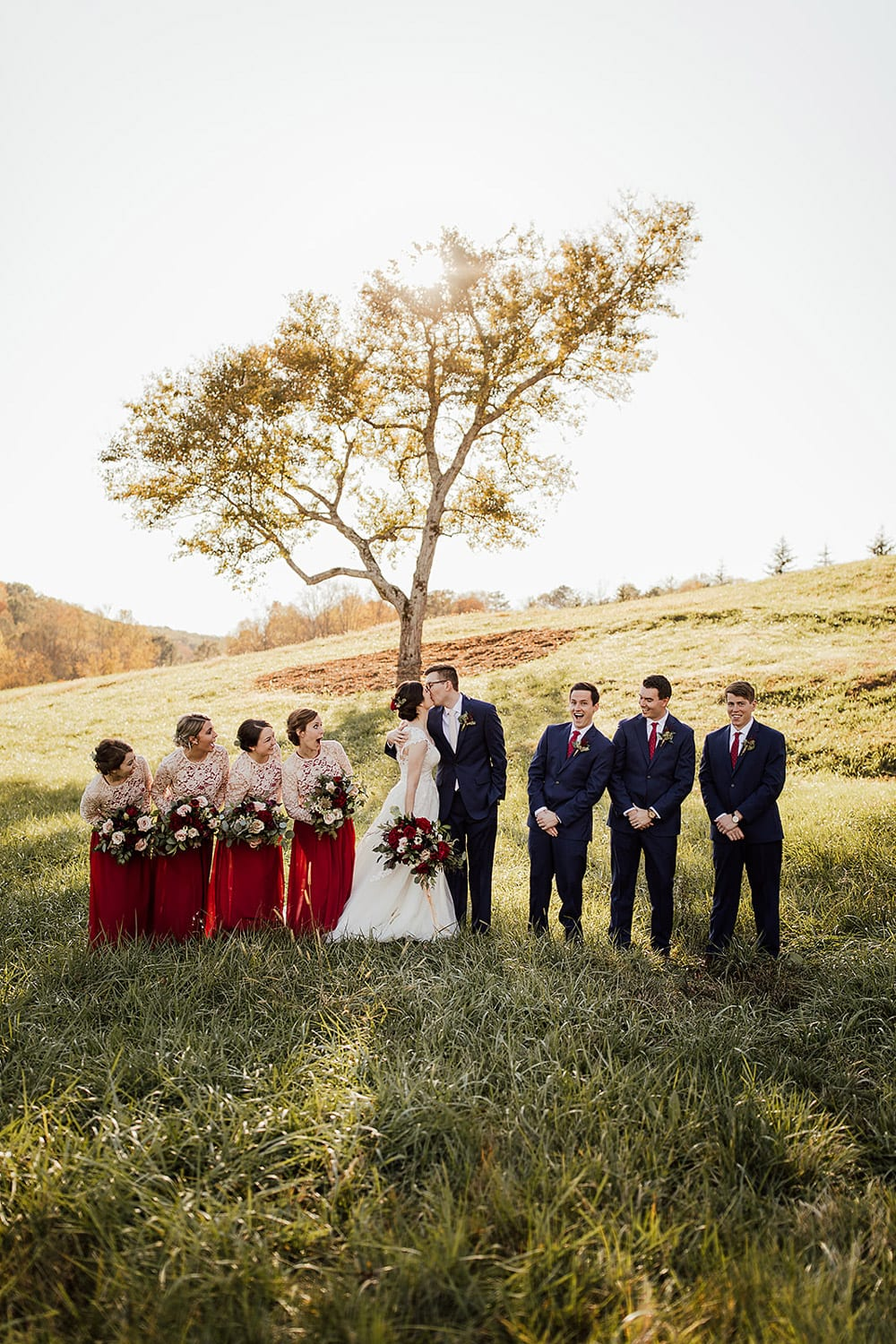 Bridal party watches bride and groom kiss in pasture
