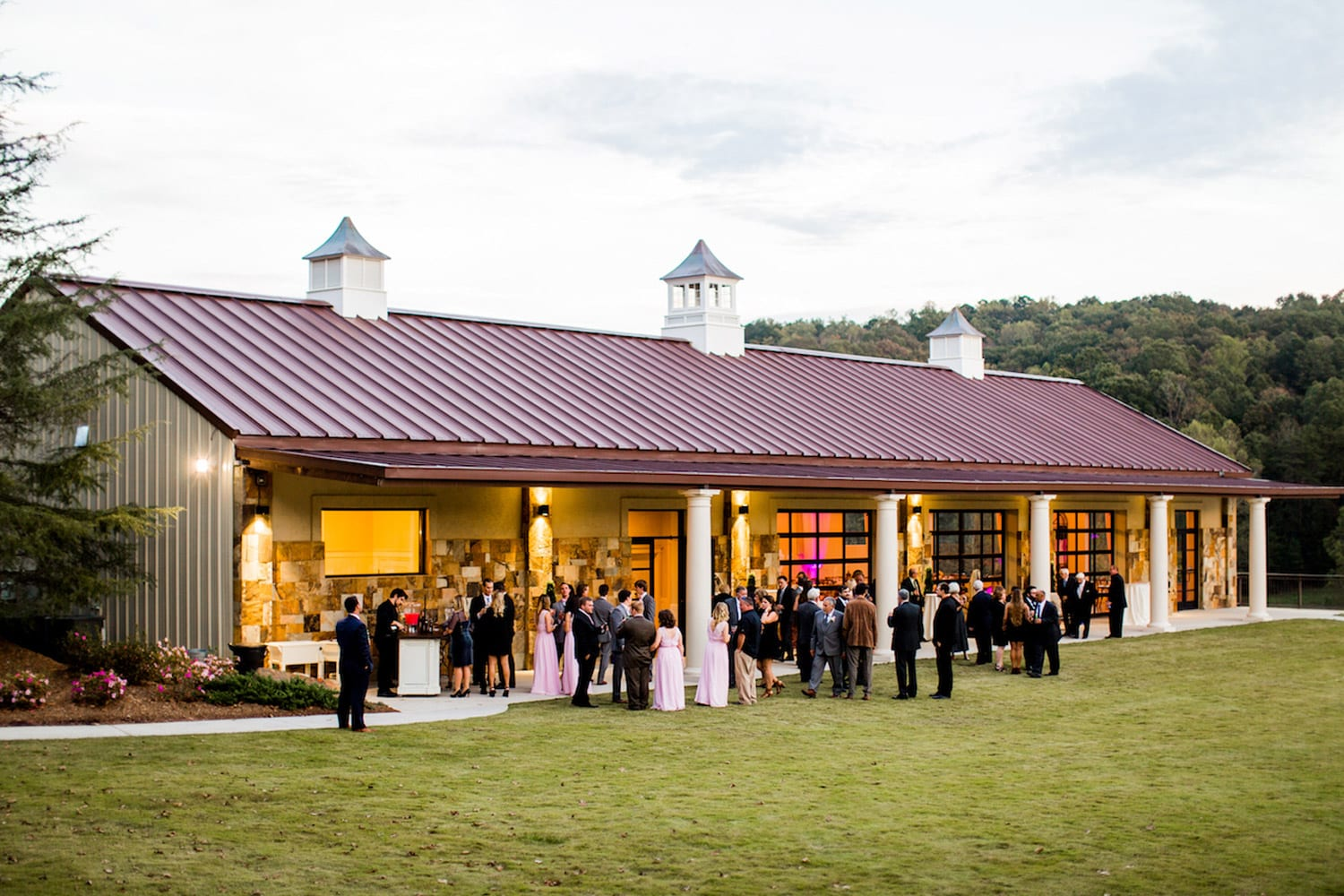 Wedding guests gather outside on the grass