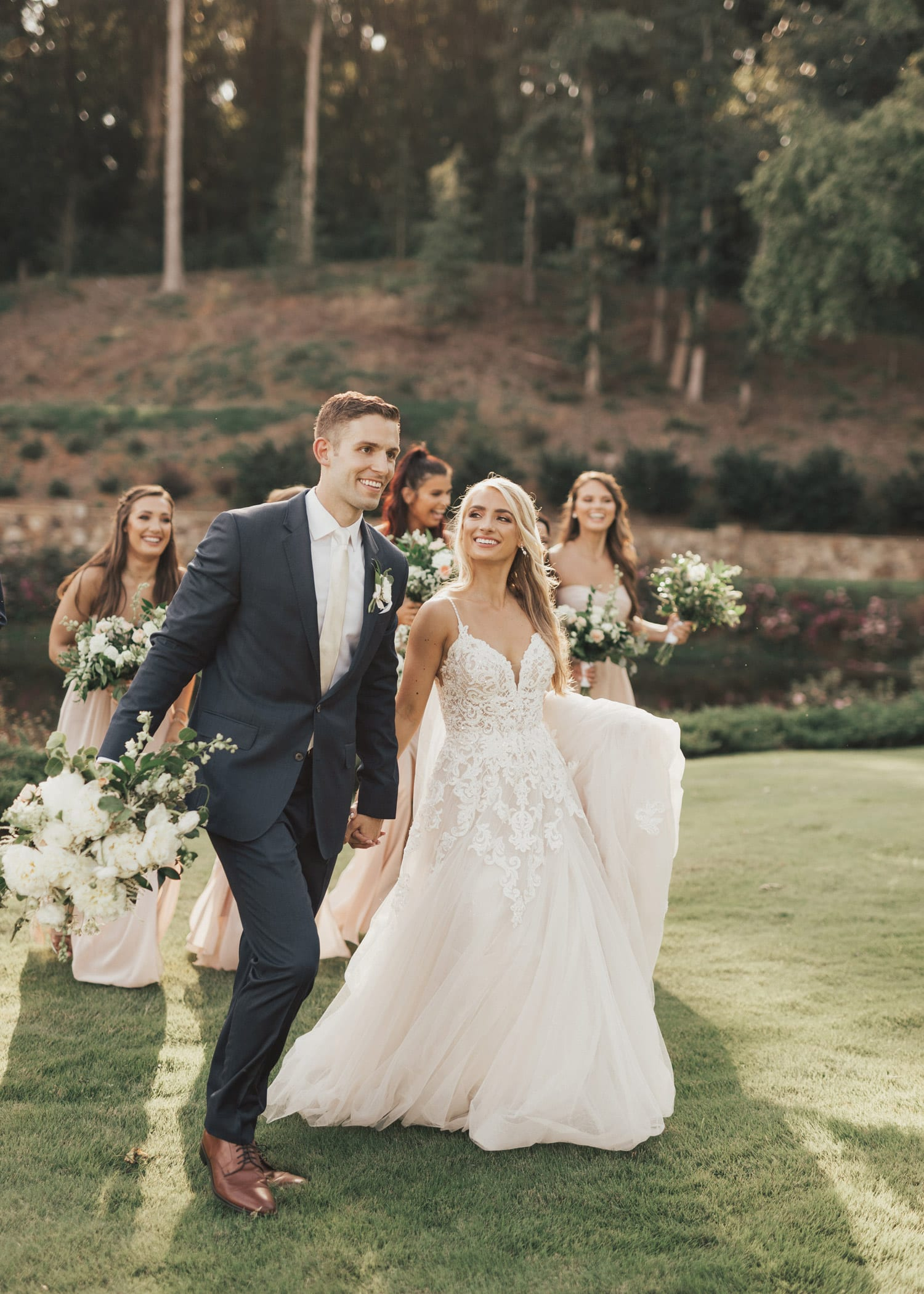 Bridal party walks along the grass