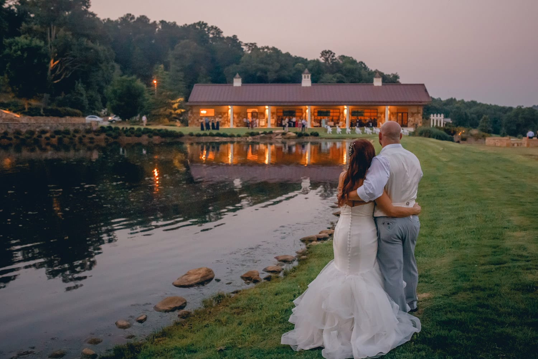 Bride and groom look across the water at wedding venue