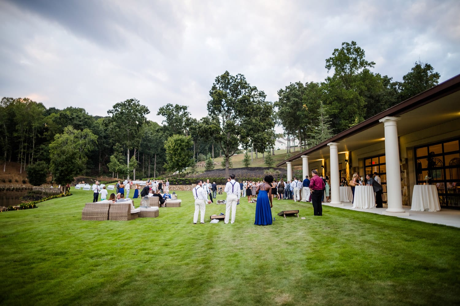 Wedding guests play outside on grass