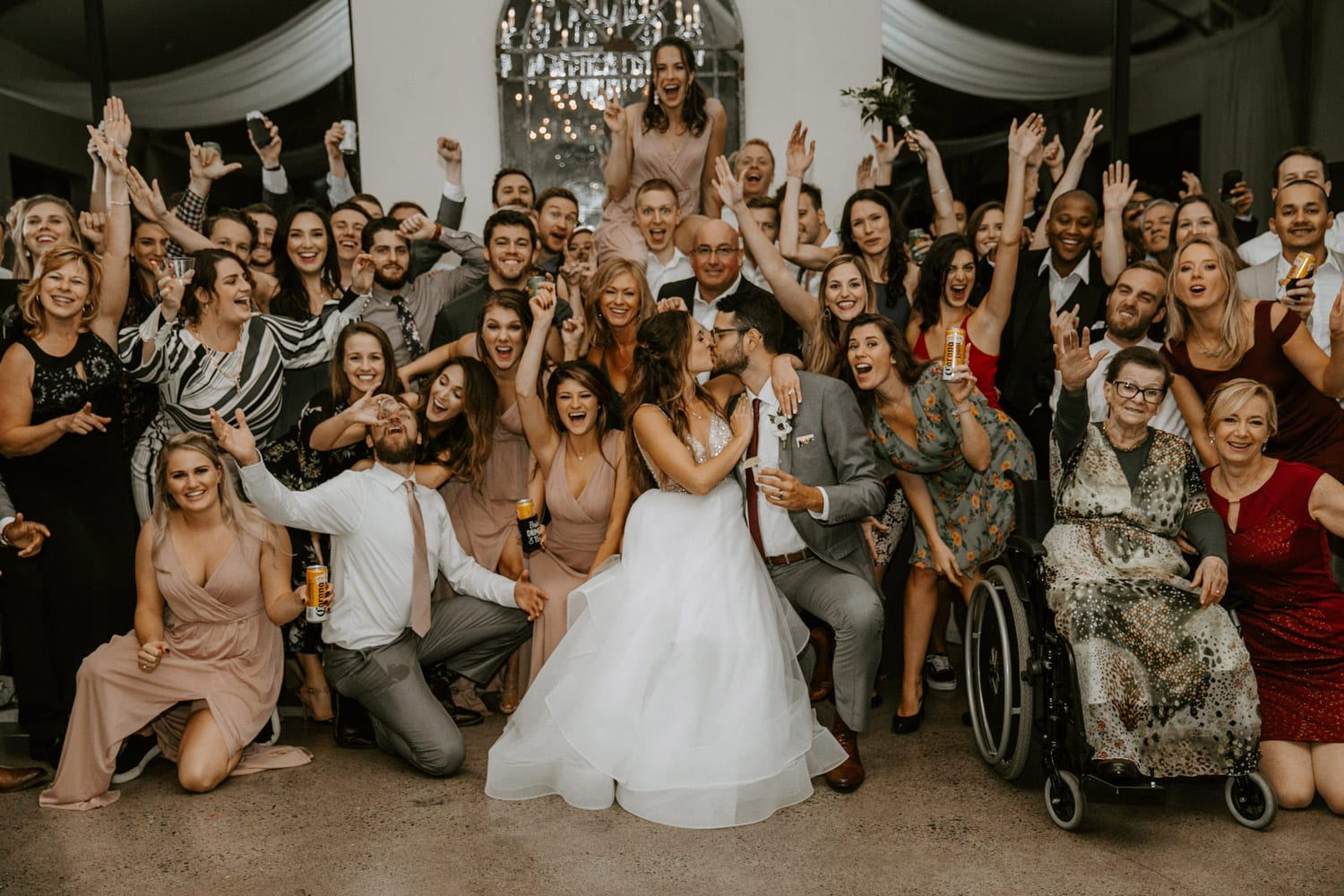 Wedding party poses by bride and groom during indoor ceremony