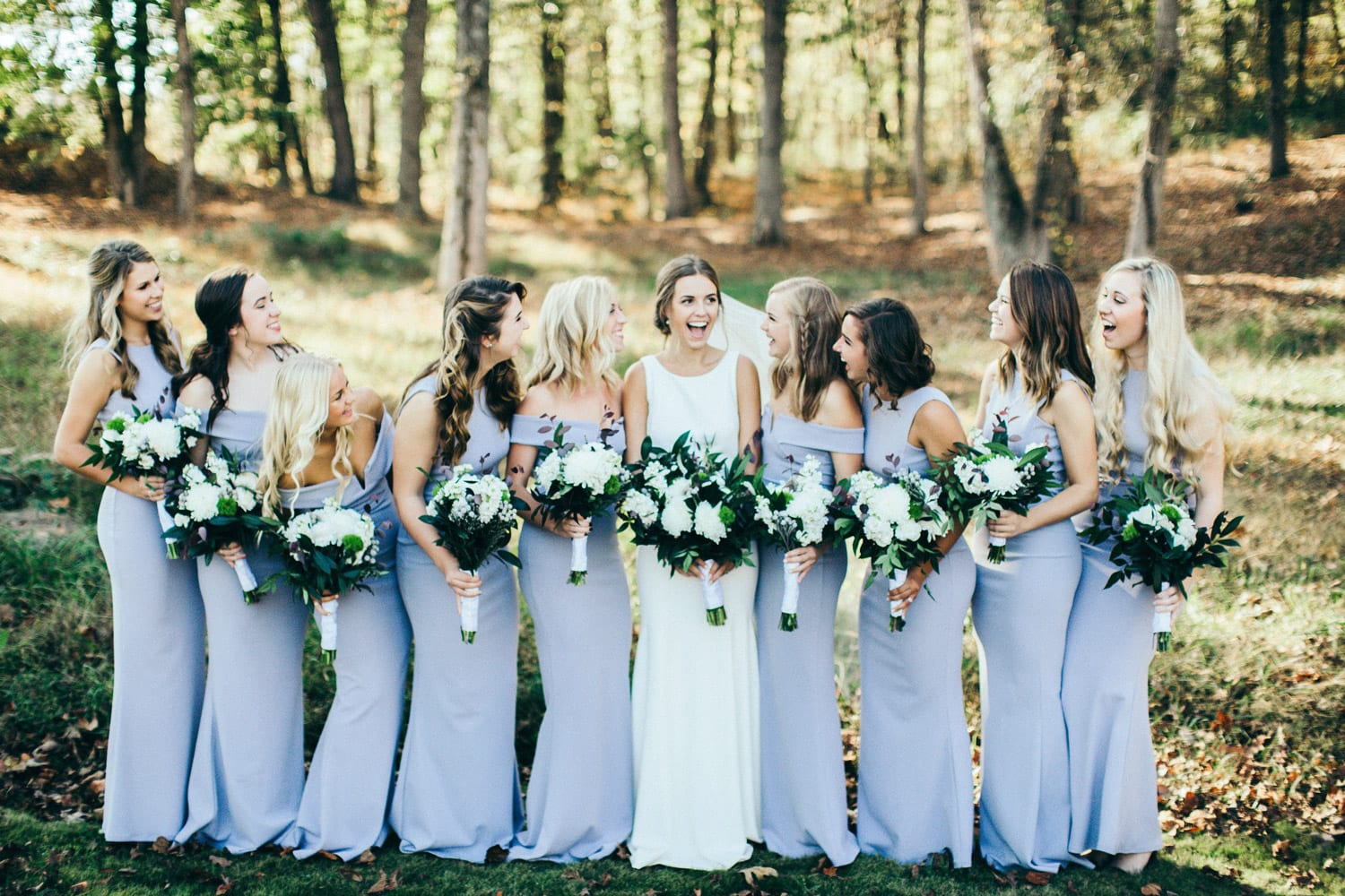 Bride and bridesmaids pose with flowers in the forest
