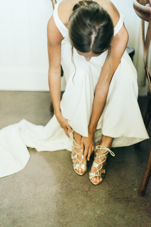 Bride puts on heels in bridal room