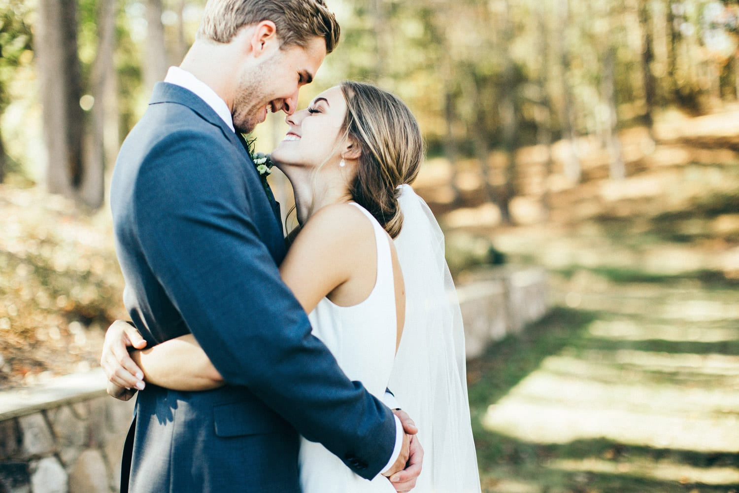 Bride and groom hold each other by stone wall
