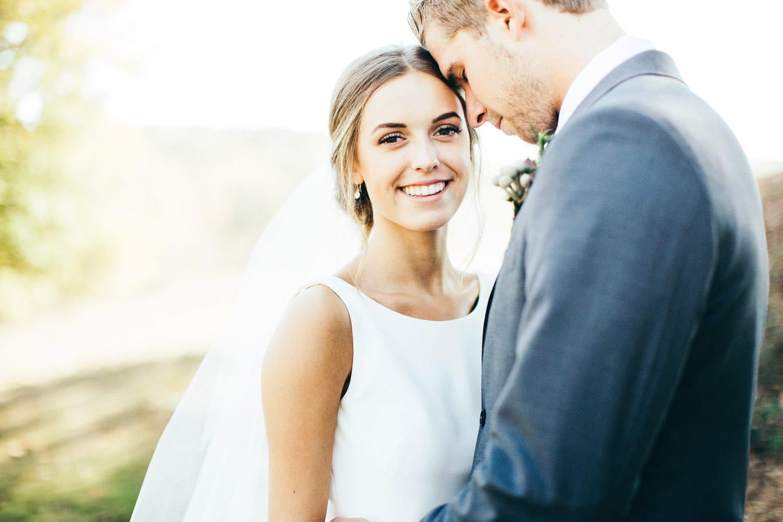 Groom holds bride outside