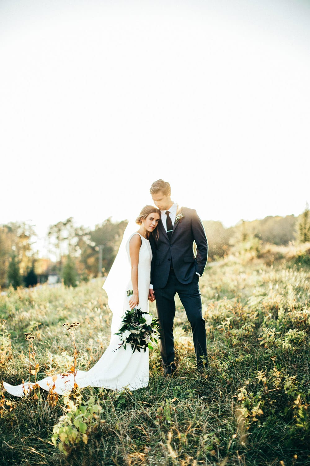 Bride and groom pose in pasture with flowers