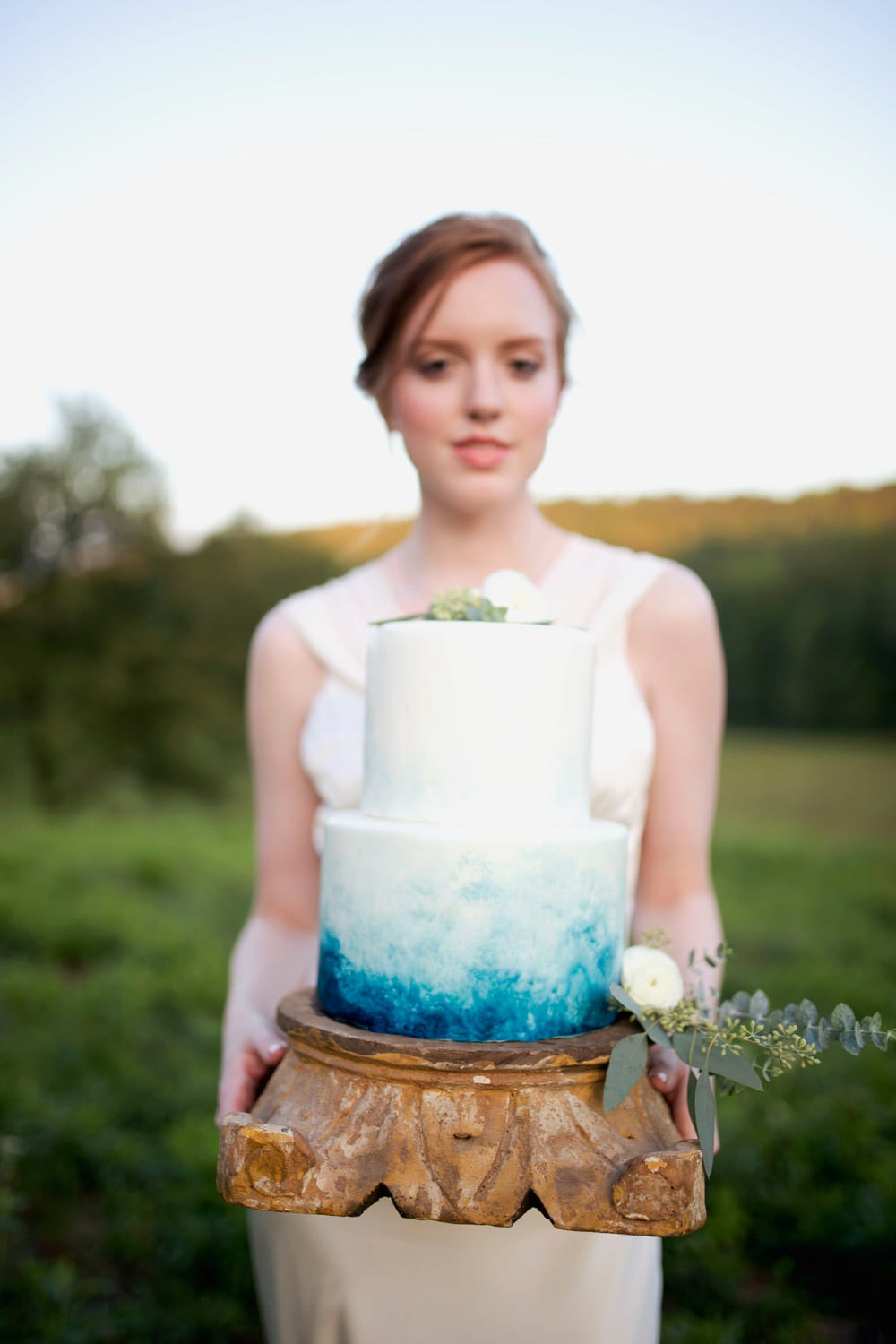 Bride holds cake in pasture