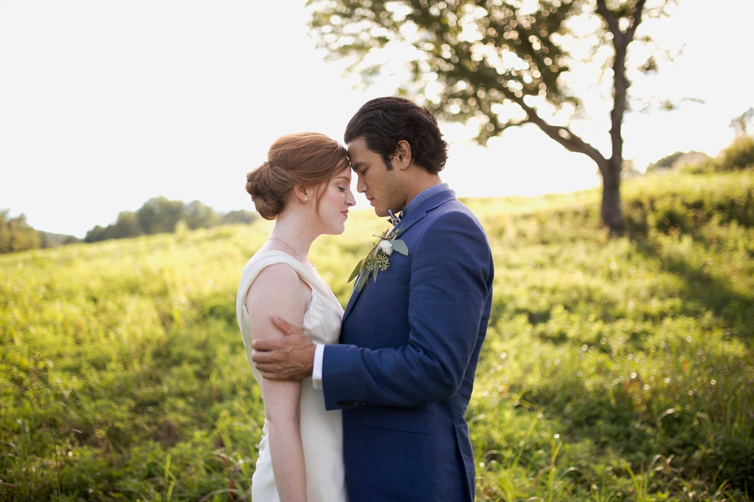 Groom holds bride in front of tree in the pasture