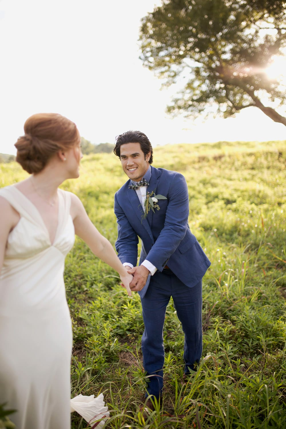 Groom follows bride by the hand in pasture
