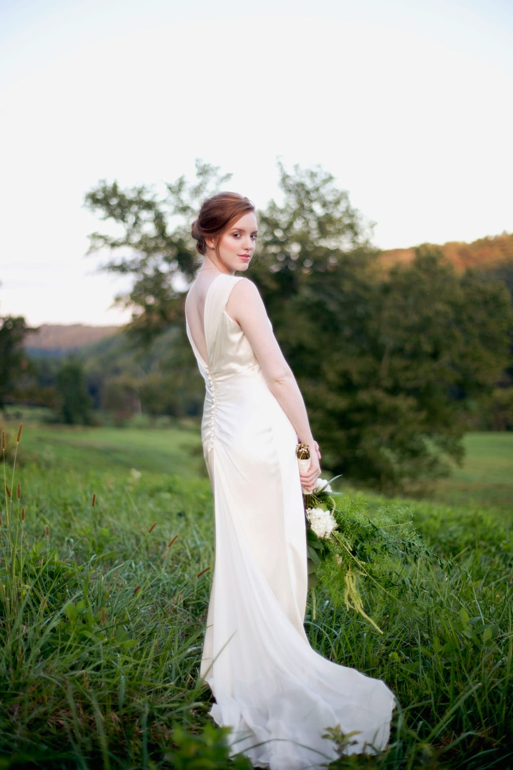 Bride poses in the pasture with flowers