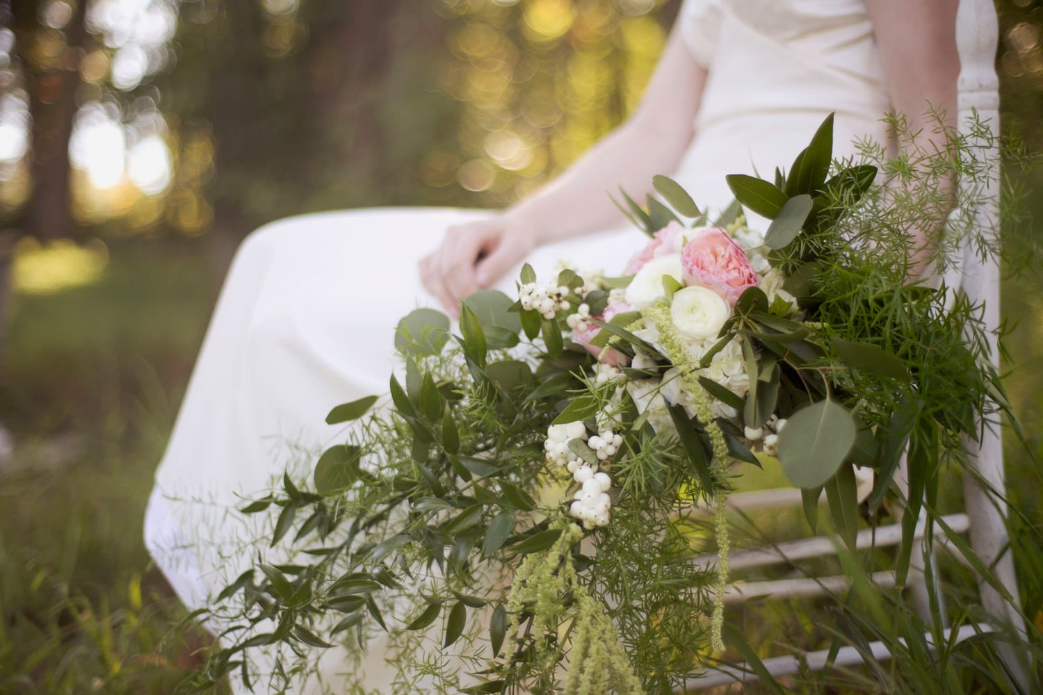Bride holding flowers on chair in the woods