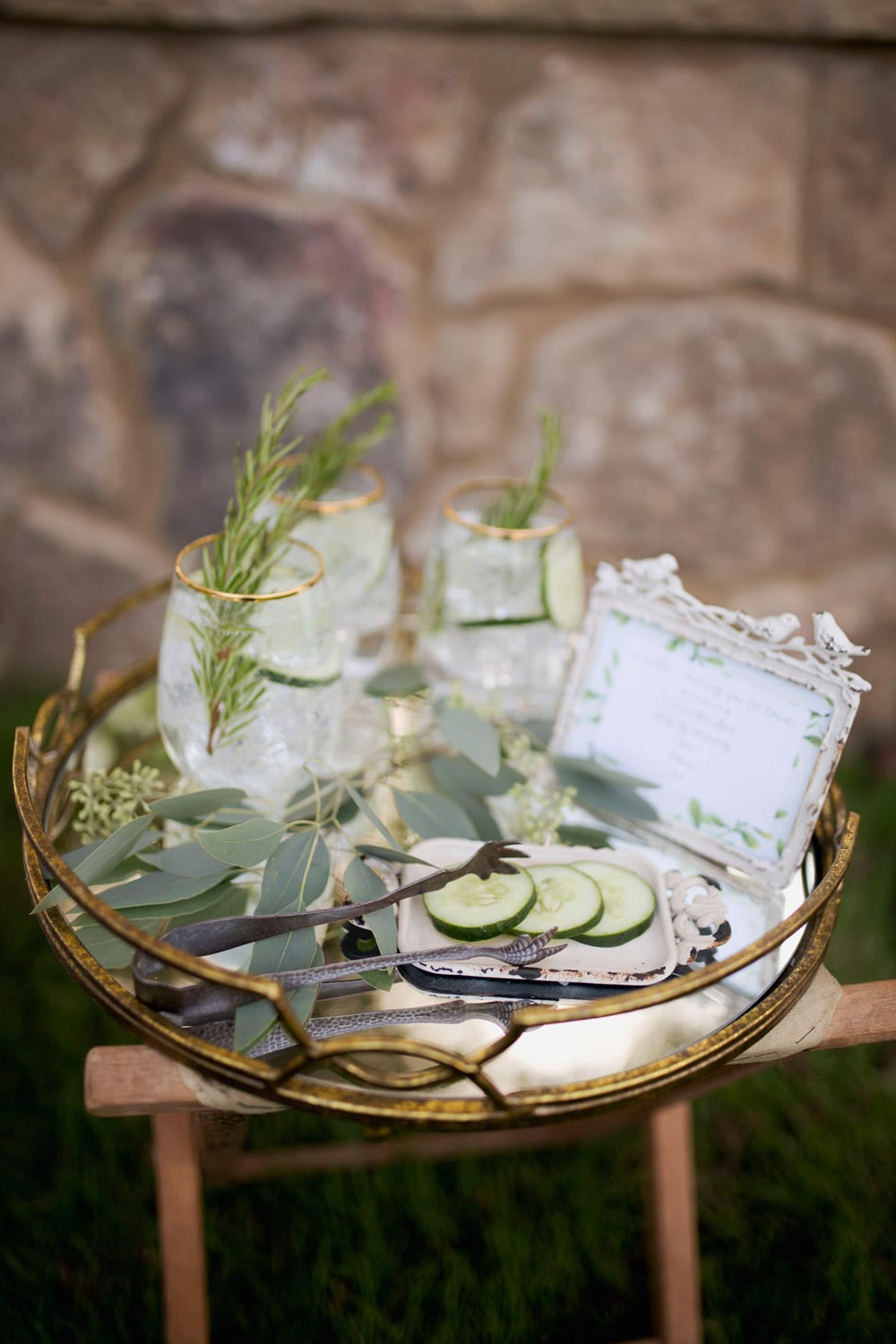 Drinks on glass table in front of stone wall
