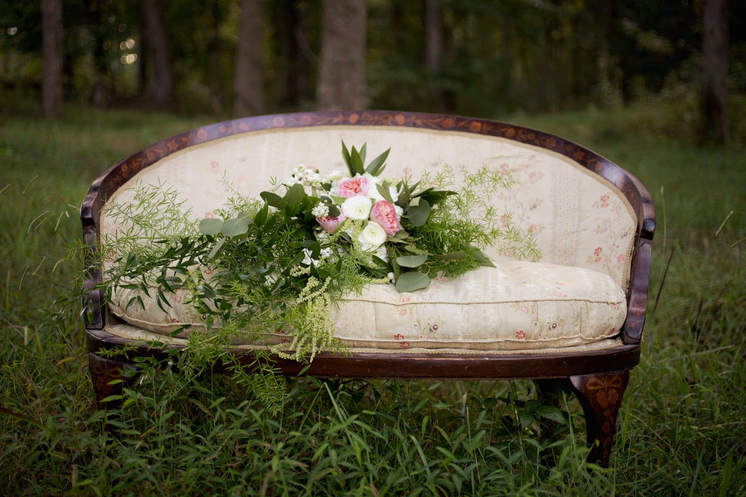 Loveseat with flowers in the woods