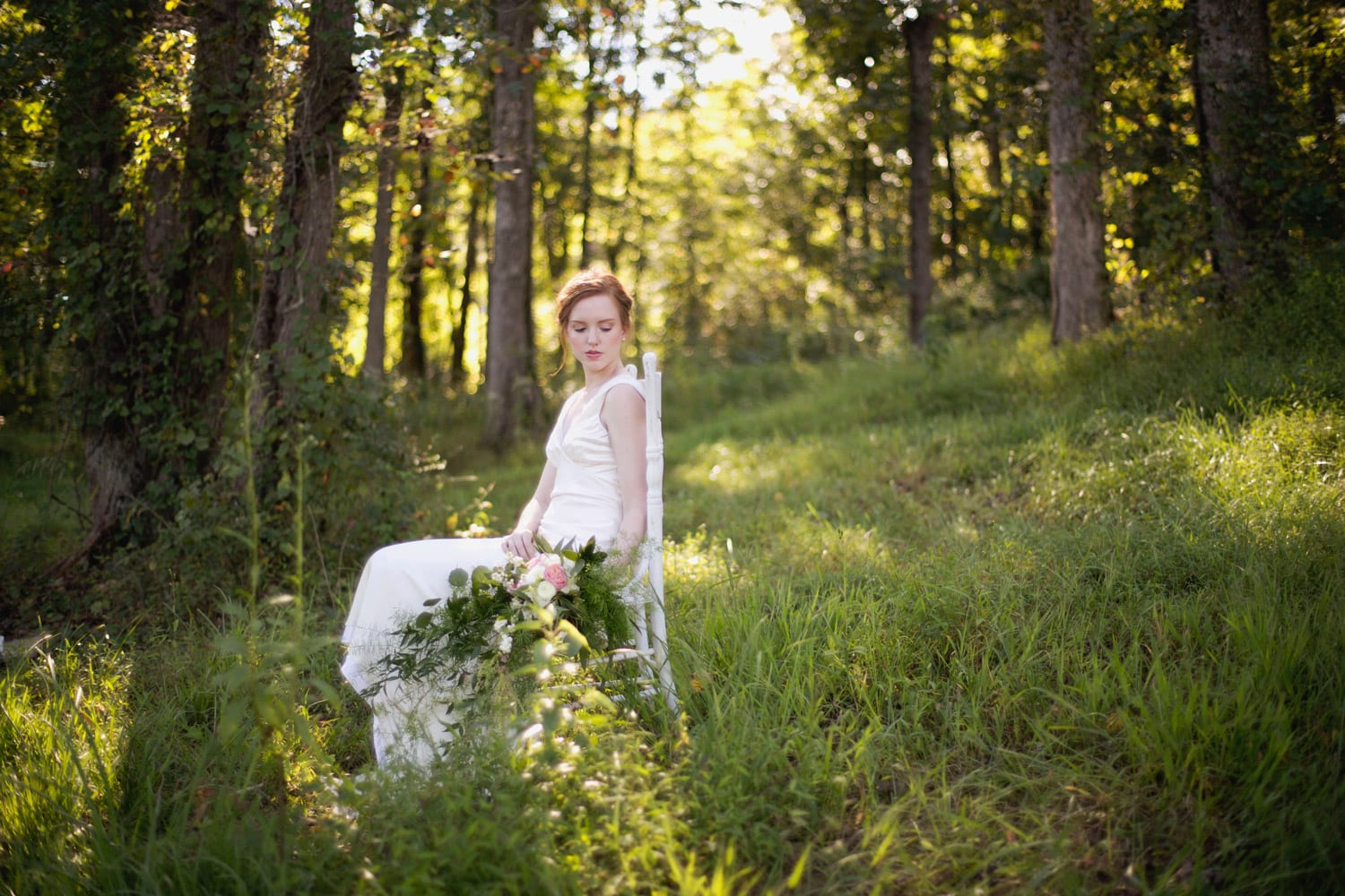 Bride sits on chair in the woods with flowers