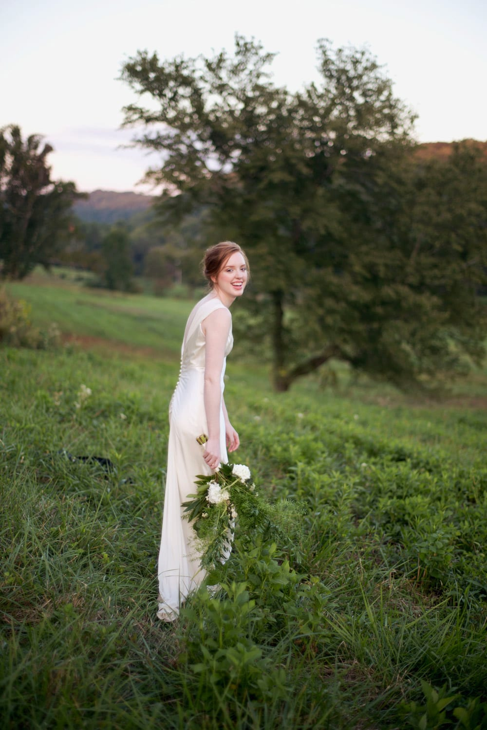 Bride holding flowers in the pasture