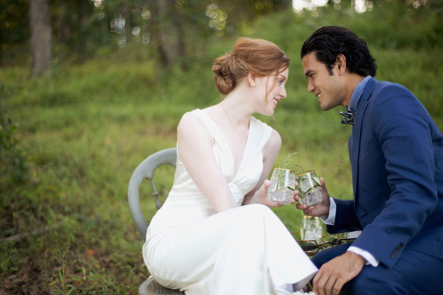 Bride and groom toast drinks in the woods