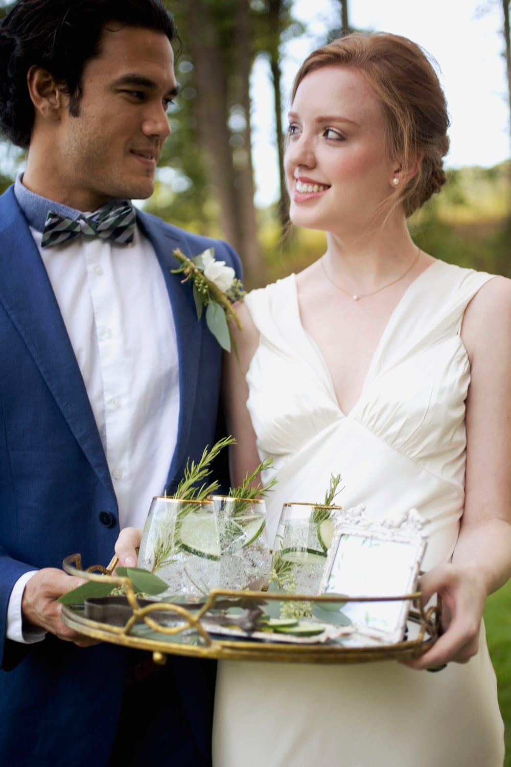 Bride and groom hold glass tray with drinks