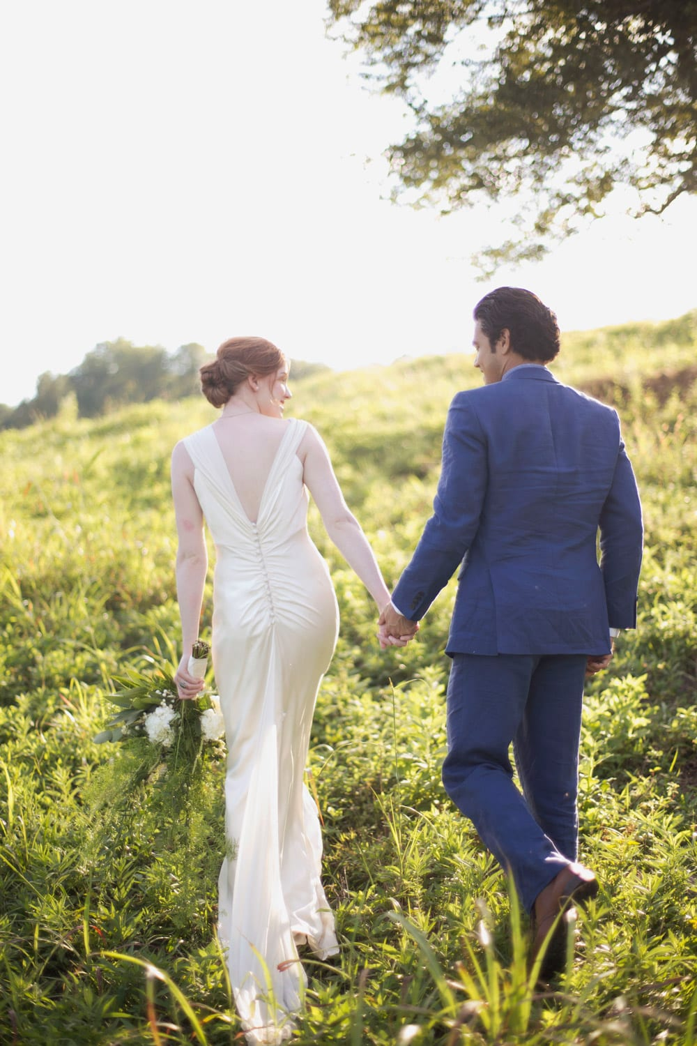 Bride and groom hold hands while walking in pasture