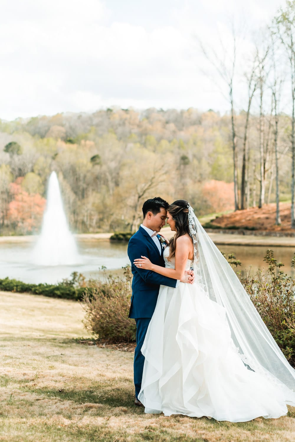 Bride and groom hold each other in front of fountain