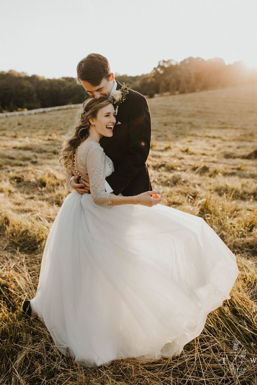 Groom holds bride in pasture