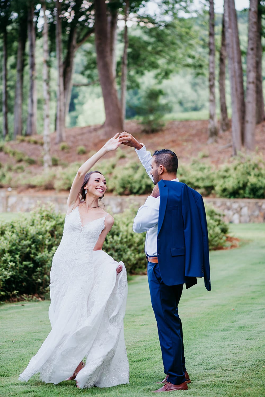 Groom twirls bride on grass
