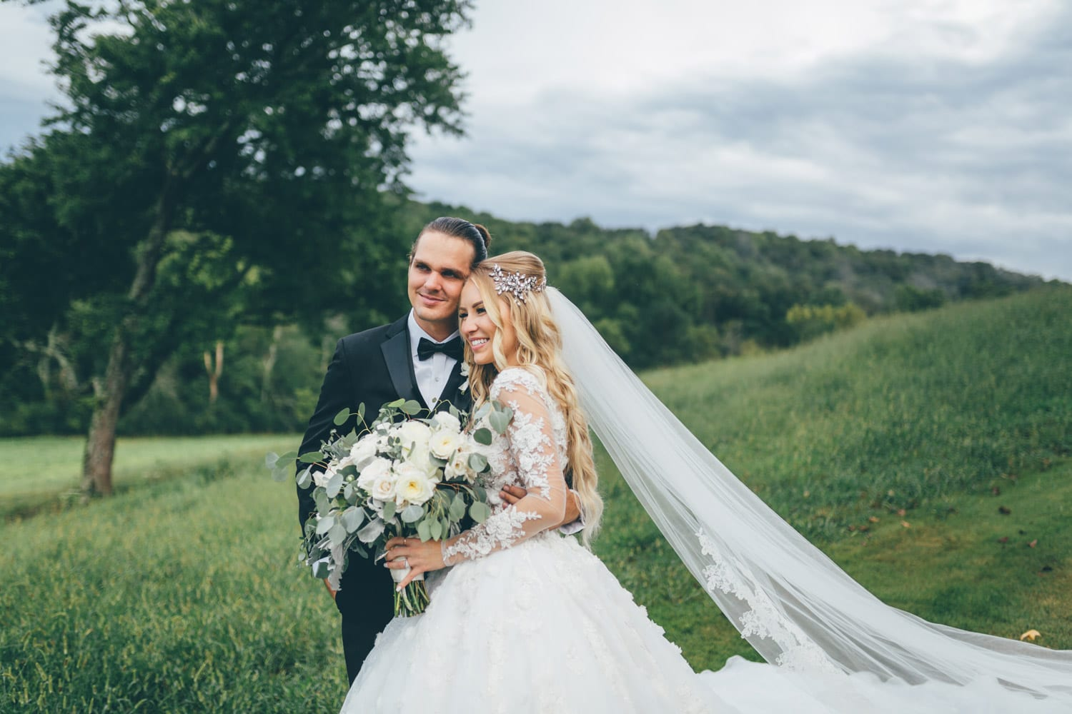 Bride and groom pose in the pasture
