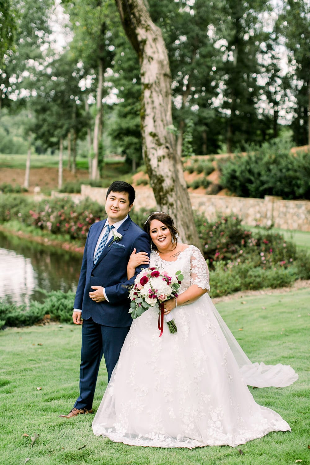 Bride holds groom's arm by the water