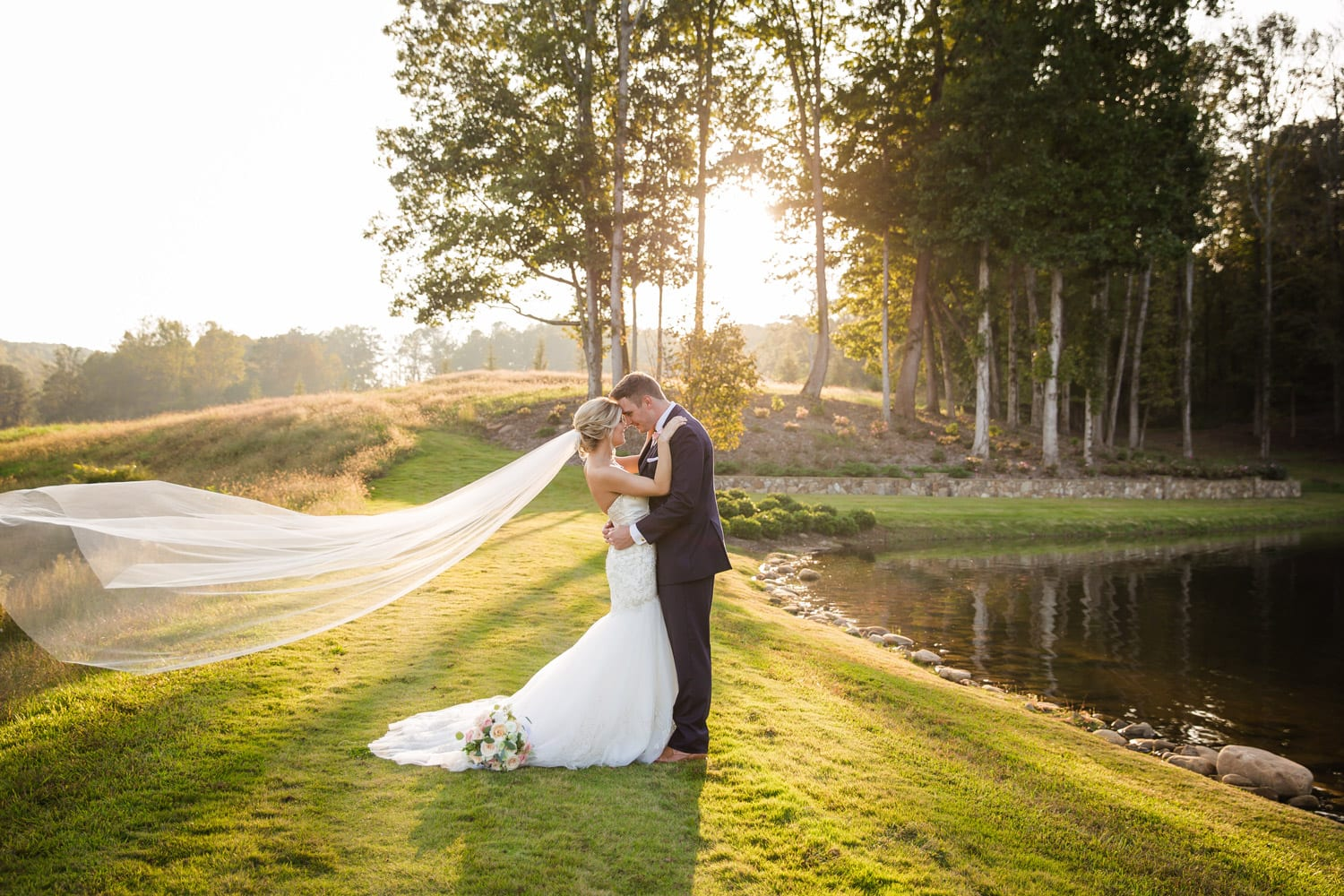 Bride and groom hold each other by the water