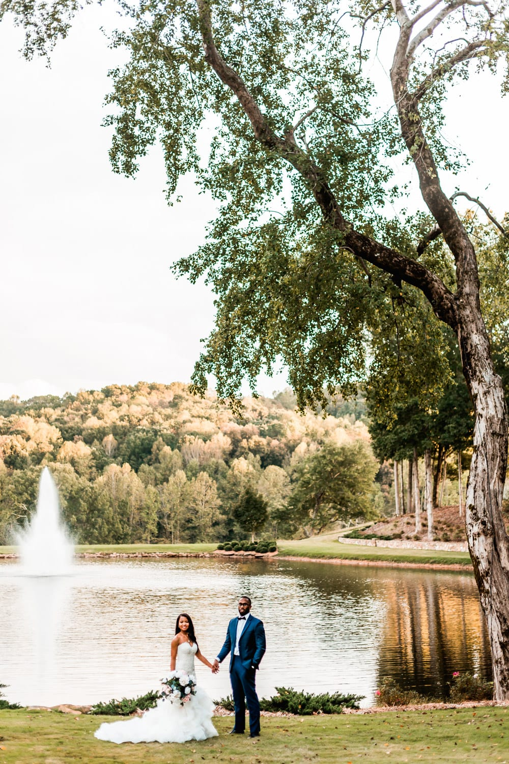 Bride and groom hold hands in front of fountain